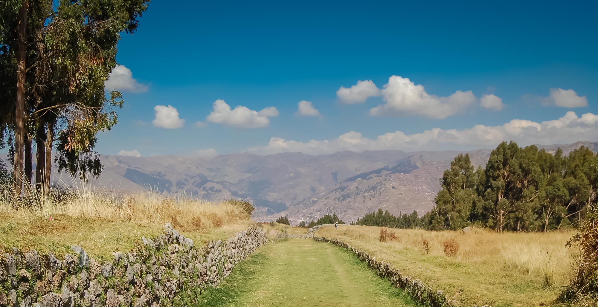 Inviting, rustic green pathway leads to a distant city on one of Peru's best tours