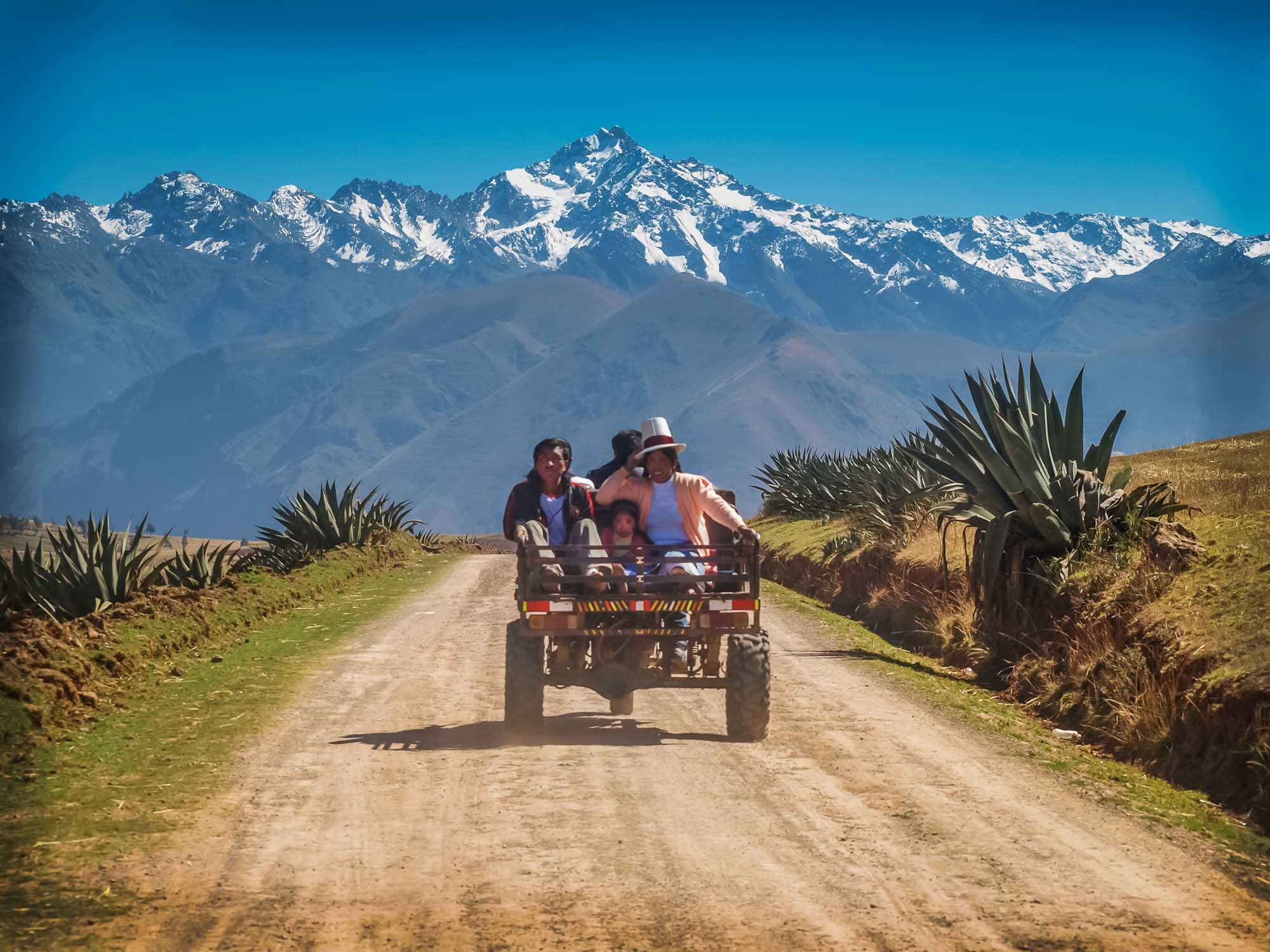 Peruvian family riding on the back of a tiny truck through a spectacular mountain landscape