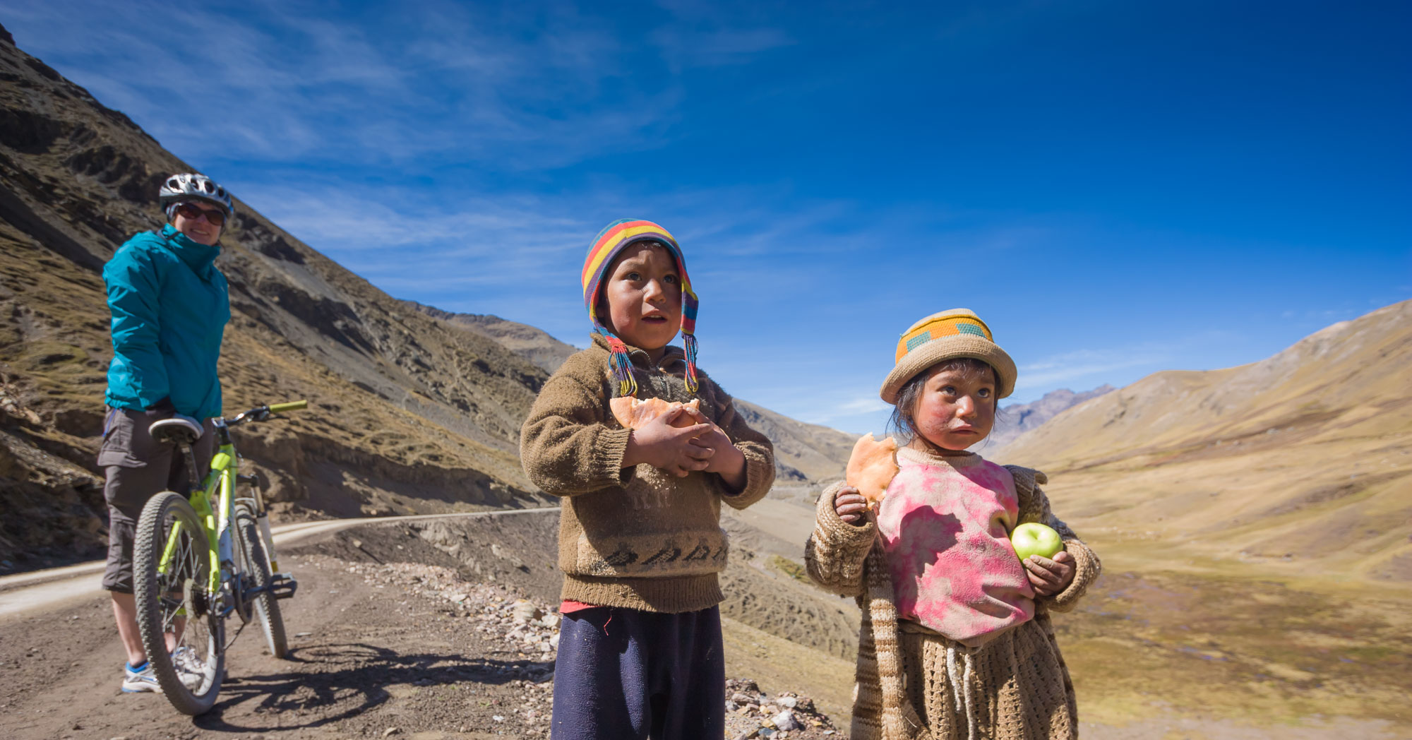 Guest on a Peru bike tour smiles at local children in the Lares valley