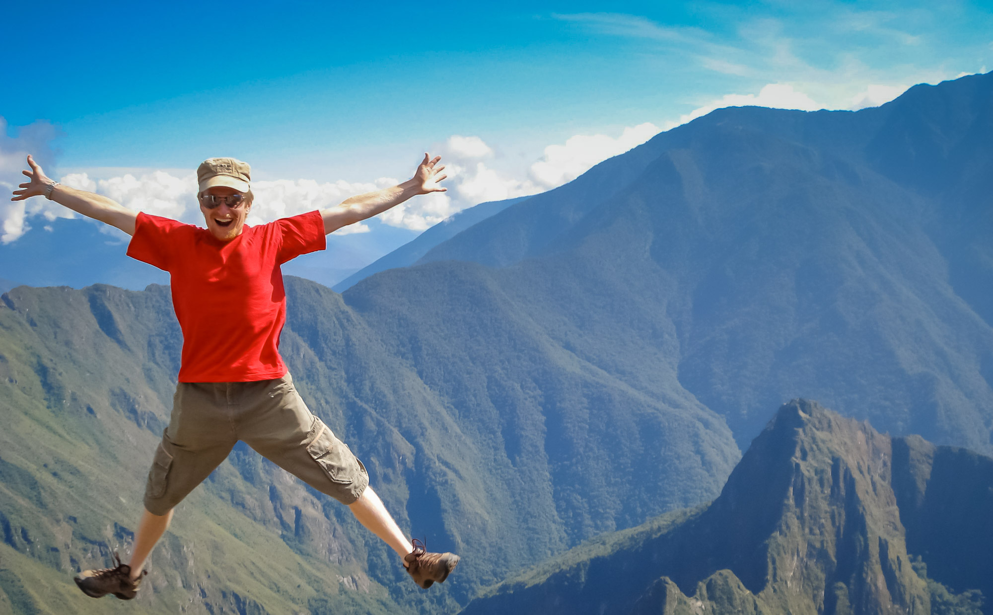 Peru adventure tour guest jumping for joy on Machu Picchu mountain