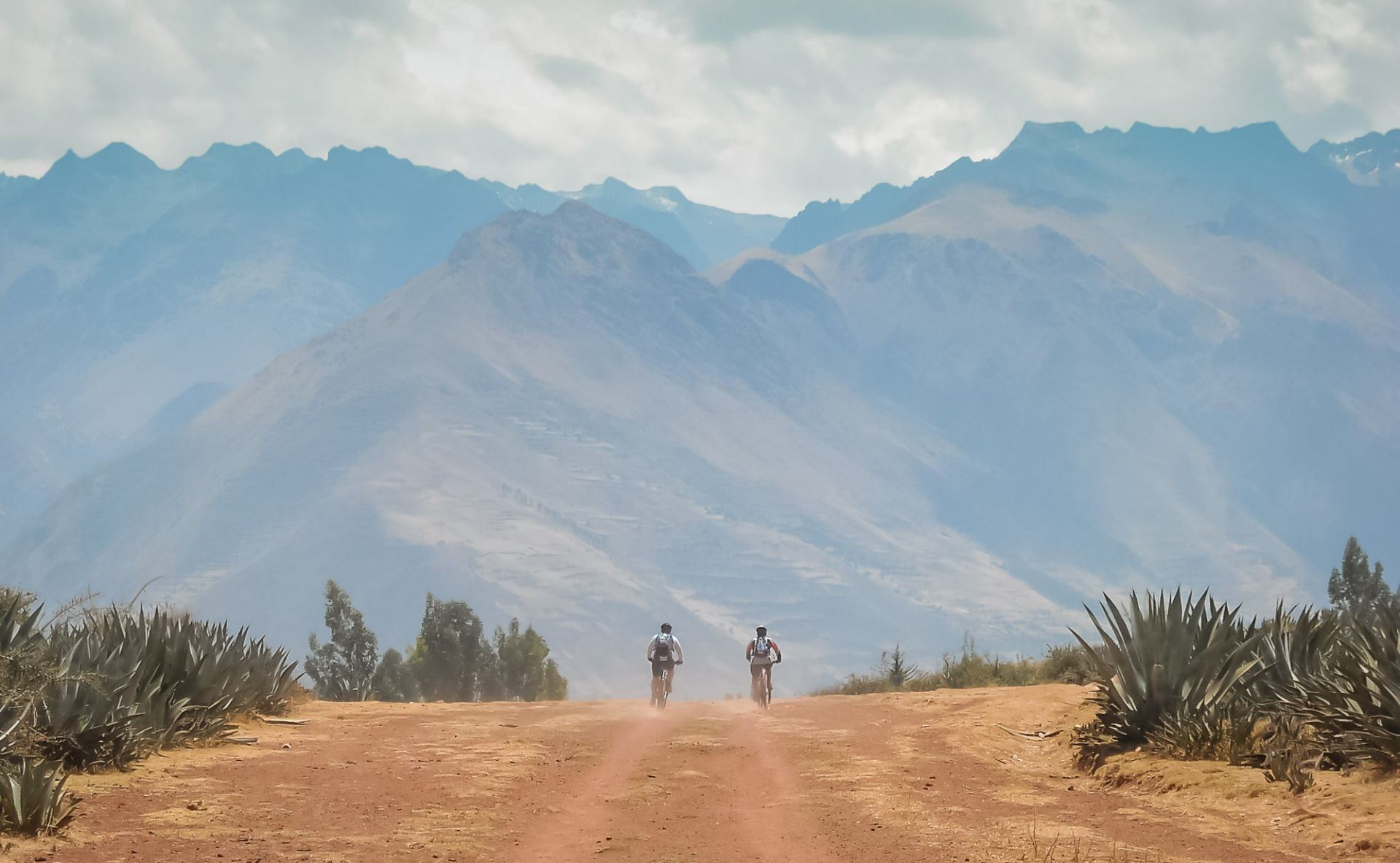 Two cyclists biking Peru on a dirt road that drops away before a huge mountain