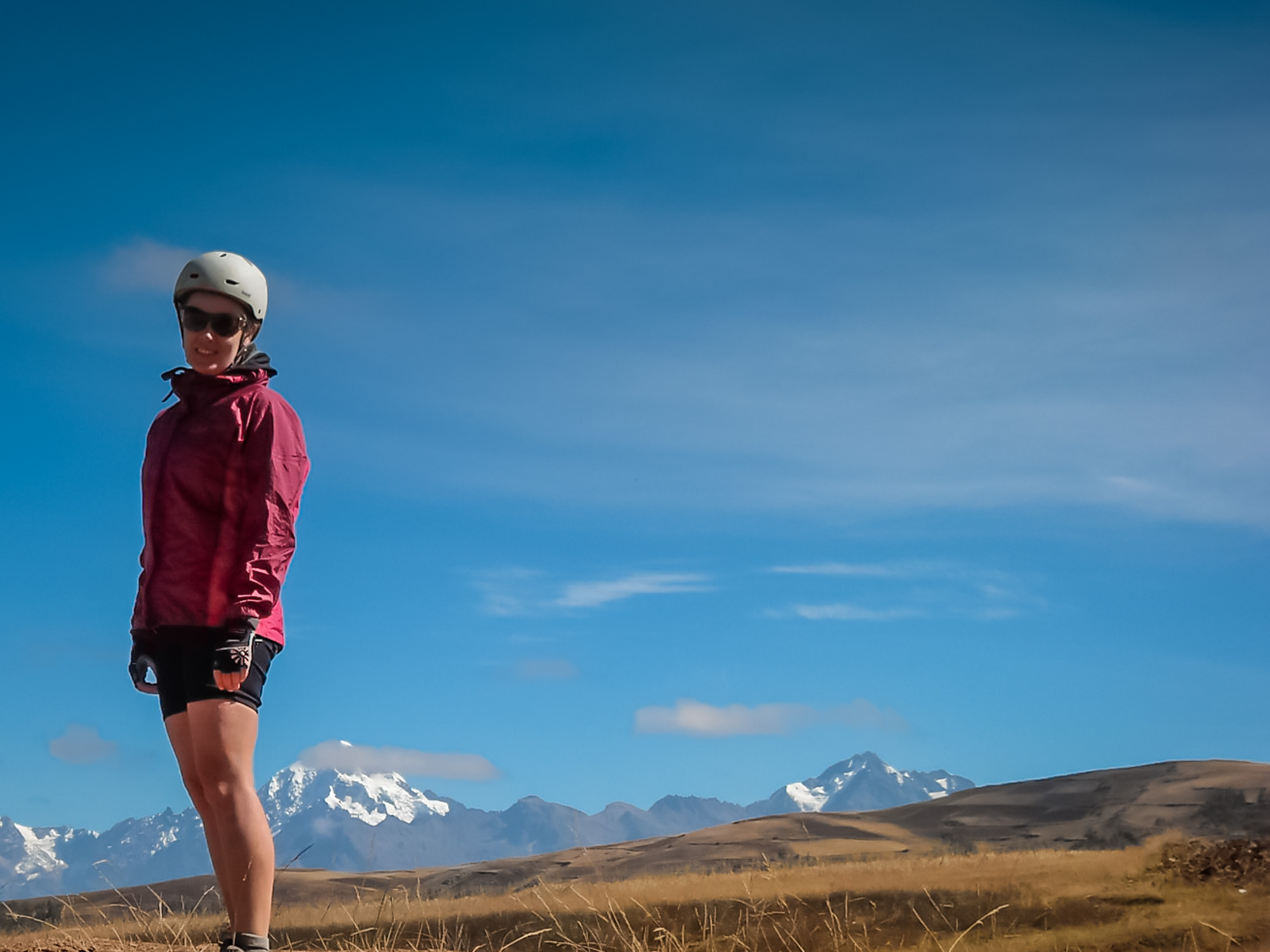 Peru guided tour guest in bike helmet in high mountain scenery